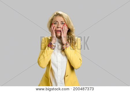 Portrait of horrified young woman. Desperate young blond woman touching her face looking confused and terrified, grey background.