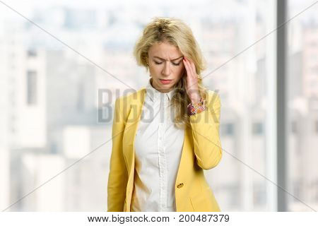 Young business woman feeling headache. Beautiful blond lady touching her head with closed eyes and having strong headache.