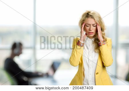 Young business woman with terrible headache. Depressed young manager touching her cheekbone and keeping eyes closed while standing against office window background.