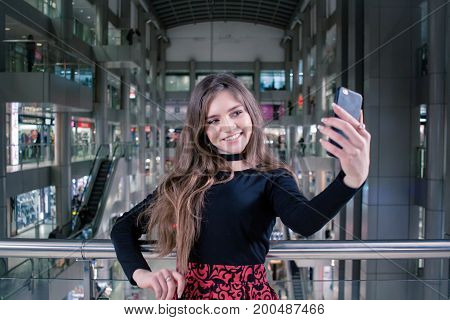 portreit of young pretty lady with cellphon in mall