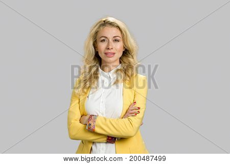 Portrait of young woman crossed arms. Portrait of smiling young business woman with crossed arms pose isolated on grey background.