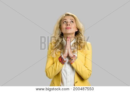 Young blonde business woman praying. Thoughtful young beautiful woman in formalwear holding hands clasped and looking upwards isolated on grey background.