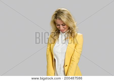Cheerful young girl looking down. Cute young woman expressing her shyness standing isolated on grey background.