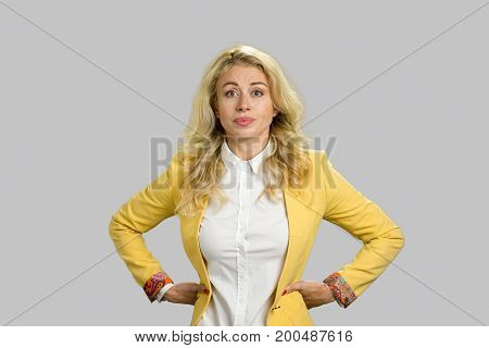 Portrait of displeased young business woman. Serious young business woman posing with hands on hips isolated on grey background.