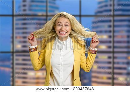 Young business woman with emotions of happiness. Delighted emotional young blond business woman showing happiness holding her hair on evening city background.