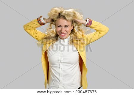 Young smiling woman, hands in hair. Shot of lovely long blond hair girl in yellow jacket posing isolated on grey background.
