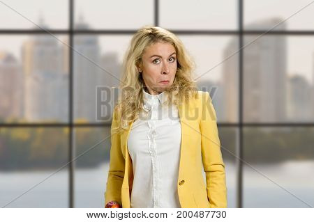 Surprised woman with funny grimace. Young business woman with stupor surprised funny face expression on office window background.