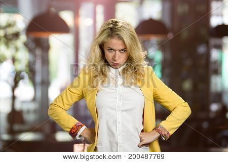Portrait of frowning young blonde woman. Pretty young blonde girl shows her anger and disagreement with a facial expression on blurred background. Angry blonde business woman keeping hands on waist.