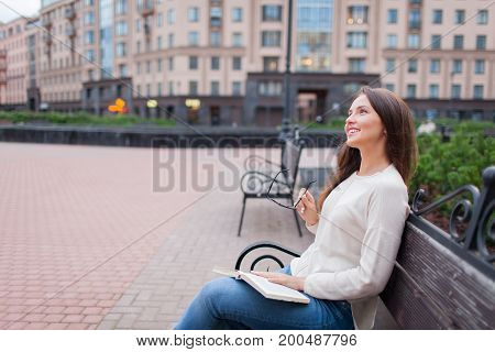 A Beautiful Young Girl With Long Brown Hair Sitting On The Bench With The Book And Eyeglasses In His