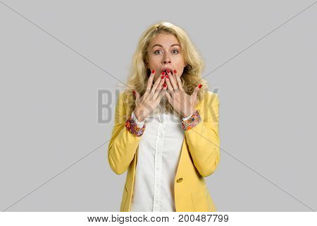 Suprised astonished young blonde woman. Shocked and surprised young blonde woman in formal wear covering her mouth with two hands, grey background.