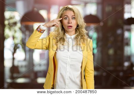 Shocked young woman touching her forehead. Surprised attractive business woman recollected something, blurred background.