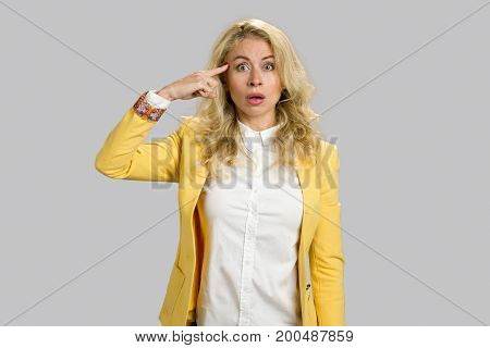 Shocked girl holding finger on temple. Portrait of surprised blonde business woman remembered something and holds a fingers on forehead, grey background.