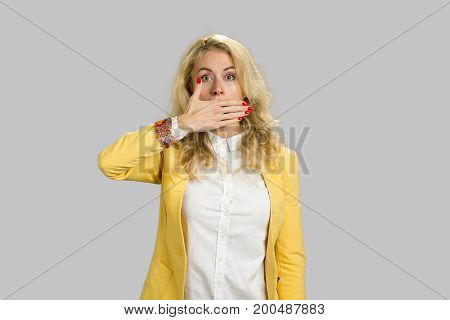 Portrait of shocked woman covering mouth. Surprised young woman covering her mouth with her hand, isolated on grey background.