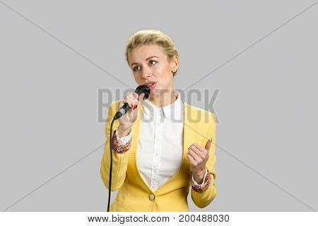 Lady with microphone looking away. Female young business trainer speaking isolated on grey background. Beautiful young woman singing into microphone close up.