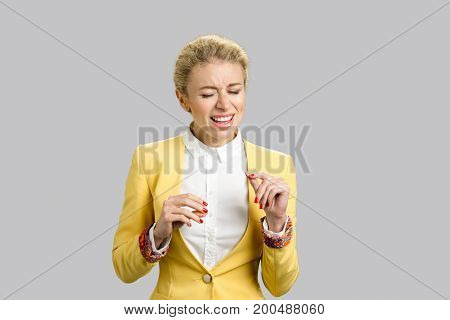 Expressive business lady singing song isolated. Emotional beautiful young woman gesturing with closed eyes on grey background. Expresive facial expressions.
