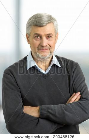 Confident mature man with crossed arms. Serious elderly man with crossed arms close up.