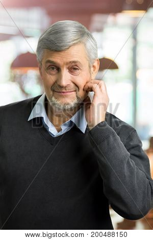 Mature man hold hand near ear. Hndsome grey hair man sitting on cafe background. Take time with pleasure.