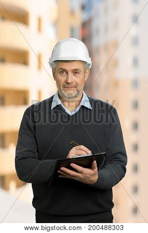 Mature engineer on blurred background. Senior architect writing on clipboard and looking straight.