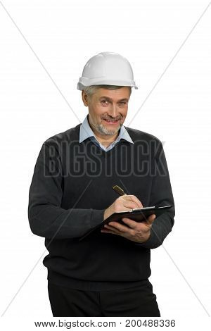 Smiling mature engineer, white background. Senior manual worker in hardhat checking new property. Mature contractor smiling and holding clipboard on white background.