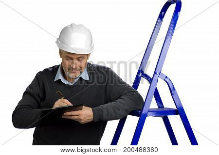 Portrait of mature building inspector. Senior engineer leaning on ladder and writing on clipboard, white background. Foreman checking new object.