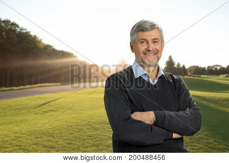 Smiling mature man on nature background. Cheerful senior man with crossed arms on landscape background. Emotion from nature enjoyment.