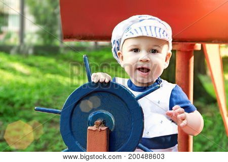 Little boy dressed up as a sailor holding the steering wheel in park.sunny