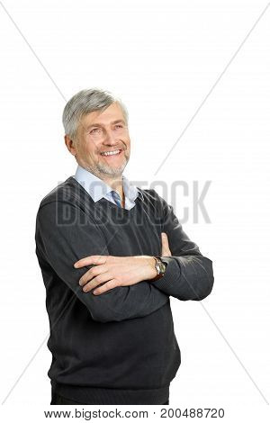 Smiling mature man with crossed arms. Portrait of cheerful senior man with crossed arms standing on white background and looking upwards.