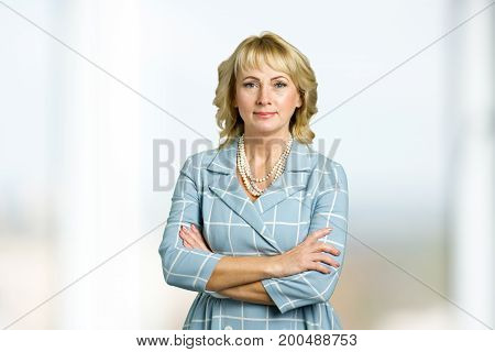 Adult woman corporate crossed arms portrait. Beautiful mature blonde in light-blue checkered dress with crossed arms on blurred background.