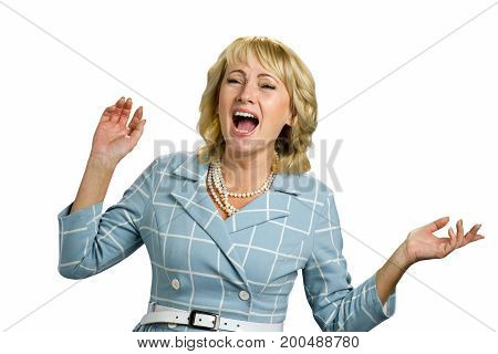 Screaming mature woman on white background. Blond adult woman with raised hands and open mouth screaming on white background close up.