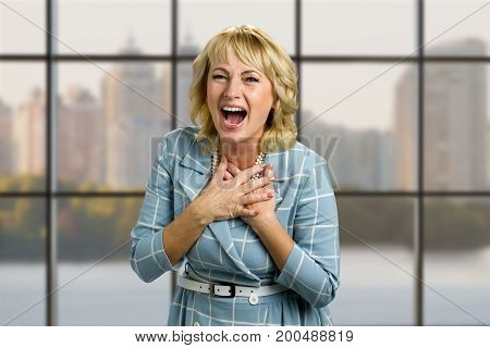 Portrait of laughing mature woman. Adult lady holding hands on chest and laughing with wide open mouth on office window background.
