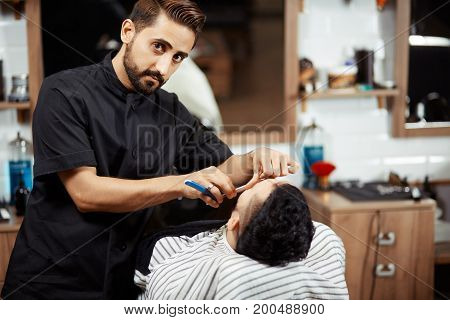 Young professional shaving man in chair and looking at camera.