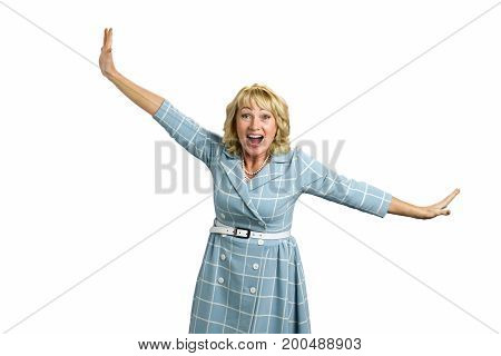 Laughing mature woman posing on white background. Cheerful white-skin woman stretching her arms diagonally, expressing happiness. Happy elderly lady posing with stretching hands in dress.