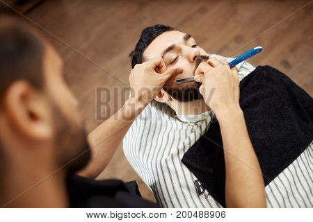 Anonymous barber shaving beard of young man sitting in chair in barbershop.