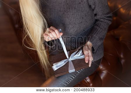 Hand Of Beautiful Blonde Girl Opening Gift. The Wood Case With Blue Bow In Blonde Girl Hands.
