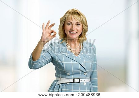 Smiling mature lady showing sign ok. Happy mature woman showing OK sign close up. Elderly lady showing everything is okay.