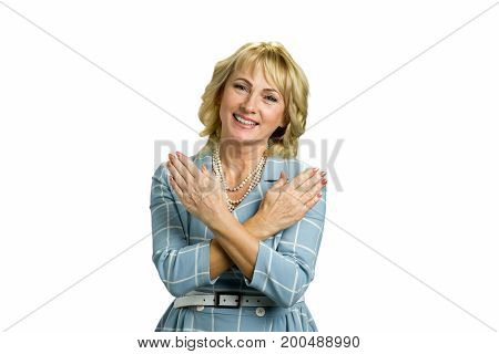 Older woman crossed arms on chest. Middle aged elegant woman smiling with hands crossed on chest isolated on white background close up.