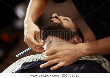 Anonymous man shaving young client with razor in barbershop.