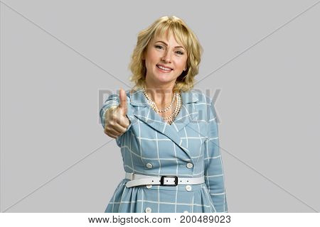 Happy mature woman showing thumb up. Smiling mature woman giving thumbs up sign isolated on grey background.