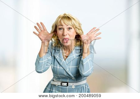 Mature woman making grimace. Cute playful white-skin blond woman making grimace looking at camera and showing tongue.