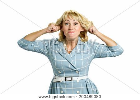 Mature woman making funny face. Middle aged woman in dress making grimace stretching ears isolated on white background.