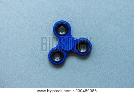 fidget finger spinner stress relief toy on blue paper background