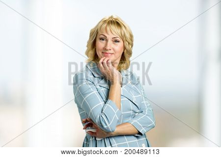 Portrait of beautiful mature woman. Middle aged lady touching her chin with hand and looking at camera. Thoughtful elderly woman.