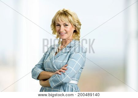 Mature woman with crossed arms. Smiling white-skin woman crossed arms, side photo.