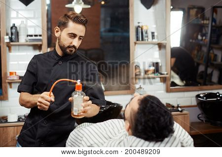 Young stylish working in barbershop and spraying perfume on young male customer in chair.