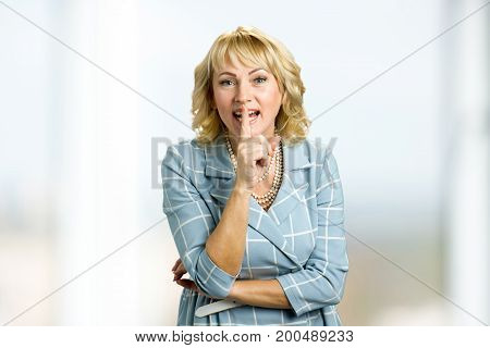 Smiling mature woman gesturing silence. Middle aged woman making silence gesture, shhhhh. Keep the silence gesture.