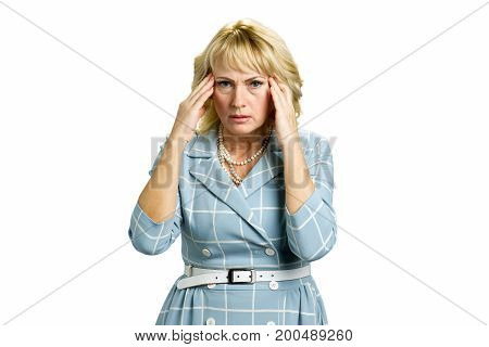 Mature woman with strong headache. Adult woman with headache holds her hands at her forehead isolated on white background.