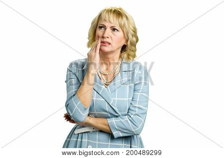 Mature woman feeling toothache. Beautiful sad mature woman suffering from strong tooth pain while standing on white background.