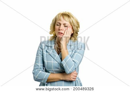 Unhappy white-skin woman suffering toothache. Beautiful middle aged woman suffering from terrible strong teeth pain, touching cheek with closed eyes standing on white background.