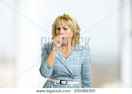 Mature woman coughing into her hand. Adult woman is coughing because having a flu. Concept of chronic cough.
