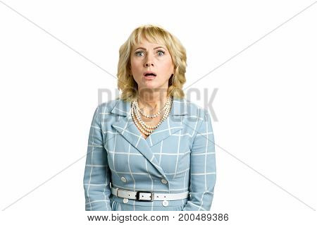 Portrait of shocked mature woman. Confused white-skin woman with open mouth on white background. Facial human expression.